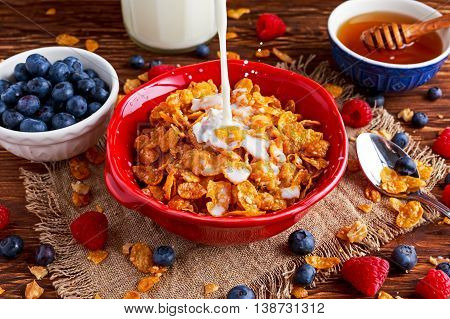 Corn Flakes with berries raspberries, blueberries with pouring milk, and sweet honey