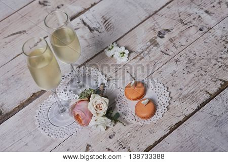 Two glasses with champagne boutonniere with roses and cookies