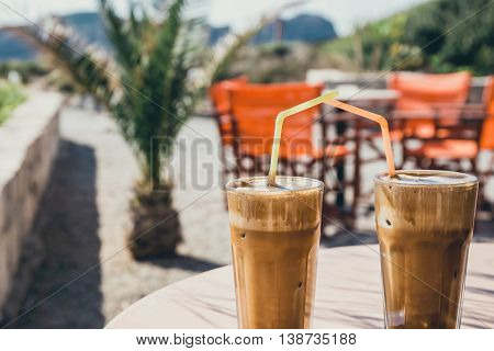 Coffee frappe greek cuisine on the table at the beach vintage look