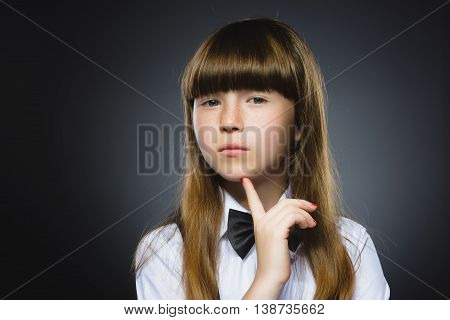 Closeup Thoughtful Young girl Looking Up with Hand on Face isolated on Gray Background.