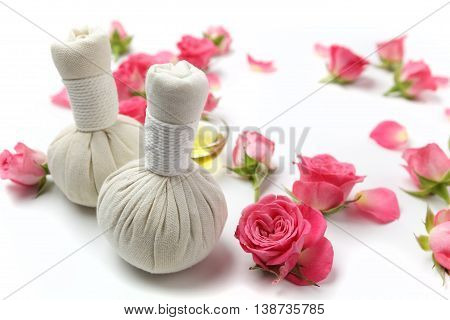 Herbal compress balls for spa treatment with rose flower on white background