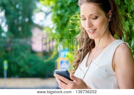 Portrait of young brunette caucasian woman with mp3 player in park