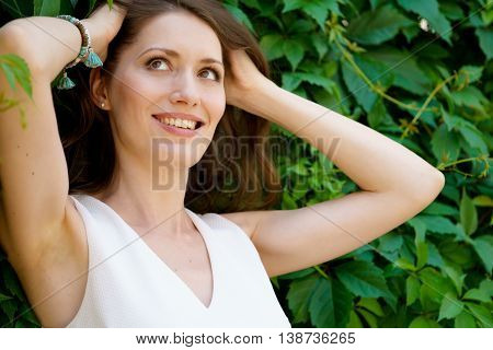Portrait of cheerful woman on background with leaves raises hair in hot summer day