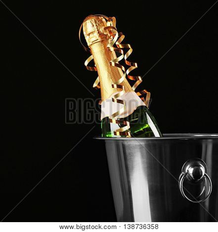 Champagne bottle in bucket on black background