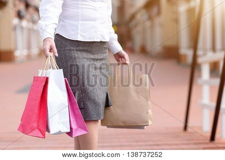 Elegant middle aged woman is going shopping. She is standing outdoors and holding packets