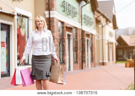 I like shopping. Joyful mature woman is walking in city and holding colored packets. She is looking at camera and smiling