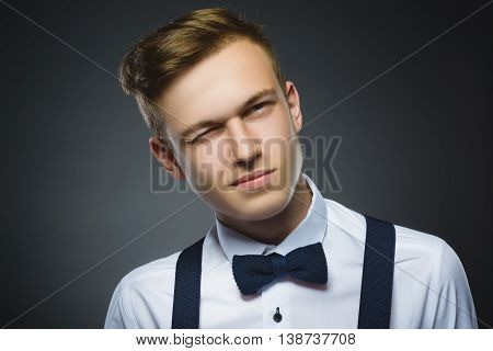 Portrait of boy winking over gray background. Positive human emotion facial expression body language.