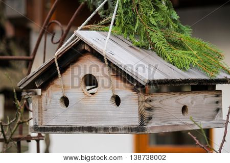 Old wooden bird house for birds in winter to feed and rest