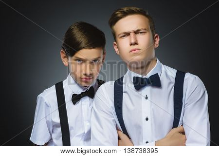 Portrait of two angry boys isolated on gray background. Negative human emotion, facial expression. Closeup.
