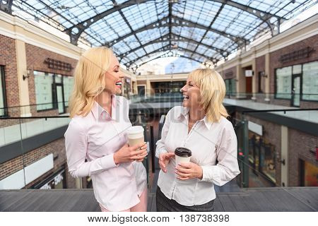 Happy mother and daughter are relaxing in shopping mall. They are talking and laughing. Woman are standing and holding cups of coffee