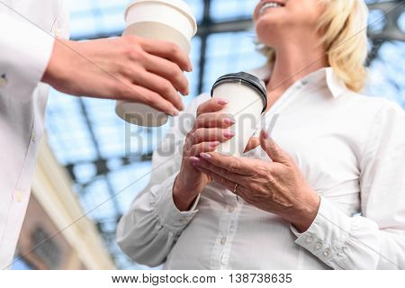 Low angle close up of female hands holding cup of coffee. Mother and daughter are standing and talking. Mature woman is smiling