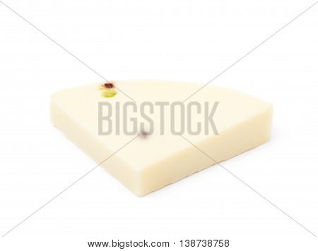 Slice fragment of white cheese with pistachio isolated over the white background