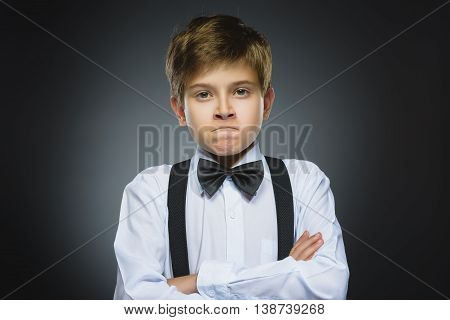 Portrait of angry boy isolated on gray background. Negative human emotion, facial expression. Closeup.