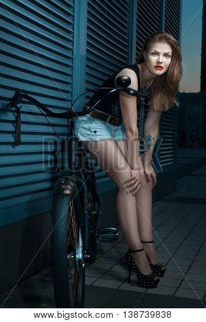 Woman in the style of rock is at night next to a bicycle cruiser.