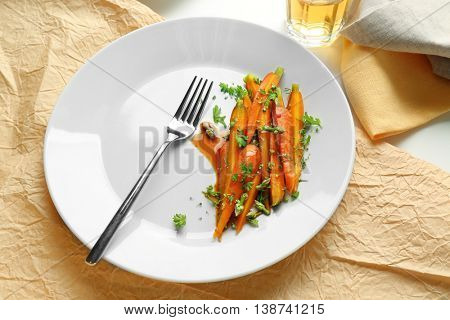 Slices baby carrots with herbs on plate closeup
