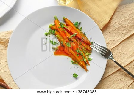 Slices baby carrots with herbs on plate, top view