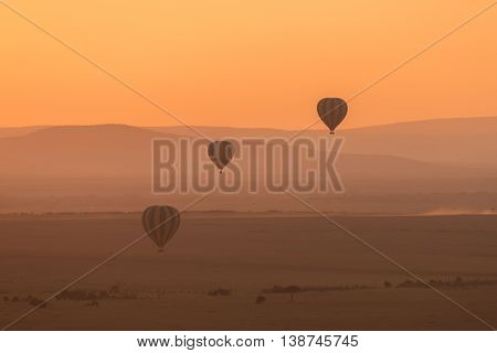 Three hot air balloons fly over the low hills of the African savannah. The aerial perspective makes the hills look different shades of purple and the sky is bright orange in the pre-dawn light.