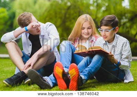 Smiling kids having fun and reading book at grass. Children playing outdoors in summer. teenagers communicate outdoor.