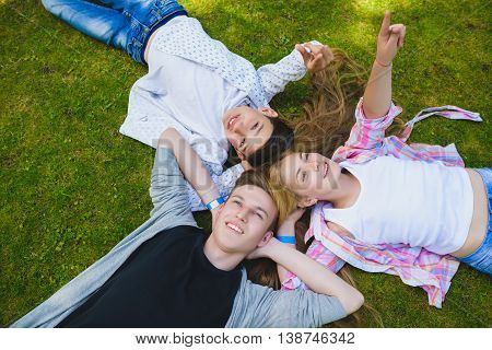 Smiling kids having fun at grass. Children playing outdoors in summer. teenagers communicate outdoor.