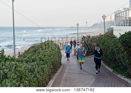 DURBAN SOUTH AFRICA - JULY 13 2016: Locals and tourists on the beach near the Millennium Pier and lighthouse in Umhlanga Rocks