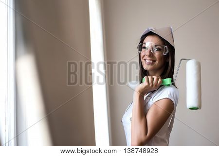 Beautiful young woman painting her Apartment with safety glasses and a paper hat.