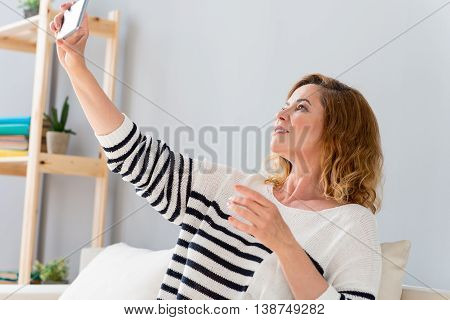 Beautiful senior woman is making selfie on mobile phone. She is looking at camera and smiling. Woman is sitting and relaxing on couch