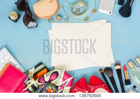 styled feminine desktop - woman fashion items on blue wooden background with aged blank paper notes