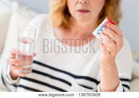 Concerned mature woman is curing illness. She is showing pills to camera. Woman is sitting on sofa and holding glass of water. Focus on medicine