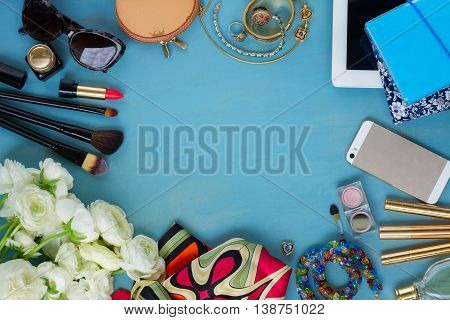 styled feminine desktop - woman fashion flat lay items and flowers on blue wooden background, copy space, top view