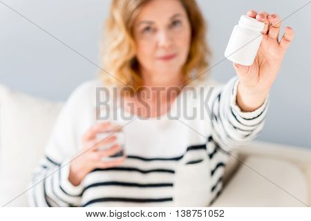 These pills will cure you. Mature woman is showing medicine to camera with confidence. She is sitting on couch and holding glass of water