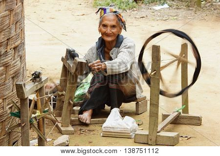 MUANG NGOI, LAOS - FEBRUARY 15, 2016: Old woman spinning on traditional spinning wheel in a minority village on February 15, 2016 in Laos, Asia