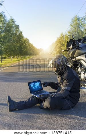 A man traveling on a motorcycle in the summer.