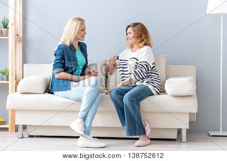 Pretty mother and daughter are enjoying friendly talk at home. They are sitting on couch and smiling
