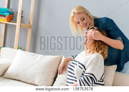 Cheerful young woman is visiting her mature mother. She is standing behind her and covering female eyes. Ladies are smiling