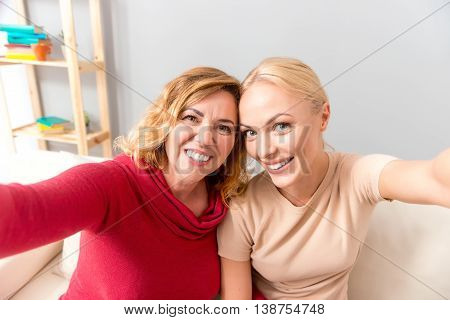 Cheerful mother and daughter are making selfie and laughing. They are stretching arms sideways. Women are sitting on sofa