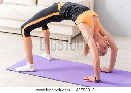 Sporty girl is making bridge posture. She is doing yoga at home. Lady is smiling