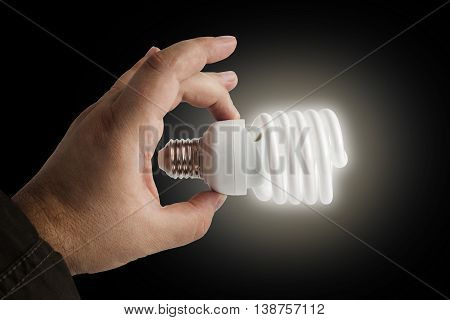 Energy saving lamp in the man's hand on black background closeup. With clipping path.