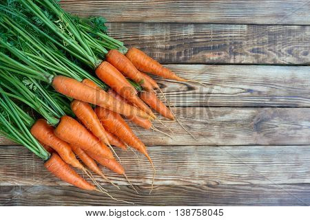 Top view, flat lay bunch of fresh carrots with green leaves over rustic weathered wooden background with copy space