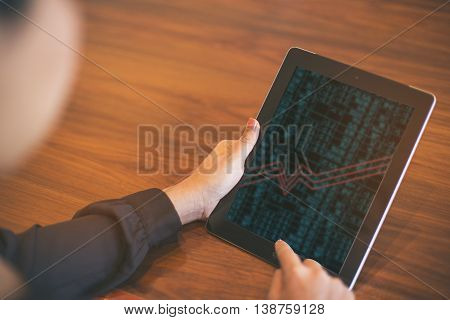 Businesswoman Checking The Stock Market On Digital Tablet In Office