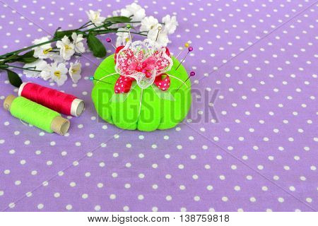 Felt pincushion with lot of pins for sewing. Background with empty place for text