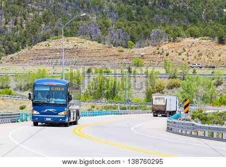 RATON, NEW MEXICO, USA - MAY 20, 2015: Greyhound Bus going to El Paso driving up an ascending road in the back a truck is driving down.