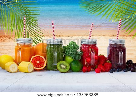 Colorful smoothy drinks in glass jars with igredients by beach