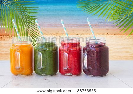 Colorful smoothy drinks in glass jars on white table by beach