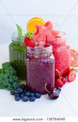Colorful fresh berry and fruits smoothy drinks in glass jars with igredients on white table close up