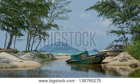Boat in lagoon. An old obsolete blue boat laying on the beach shore of a lagoon. Tropical scene looking like paradise taken on the Vietnamese island Con Dao.
