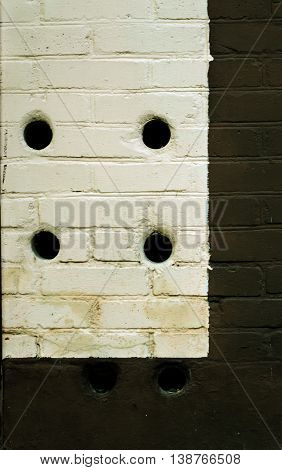 White and black painted brick wall with six holes
