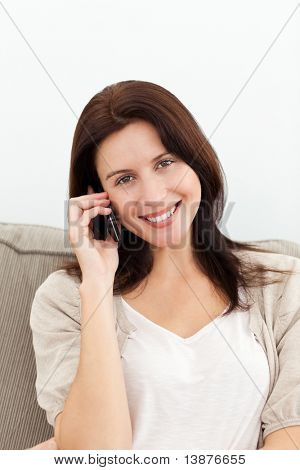 Lovely woman on the phone sitting on the sofa at home