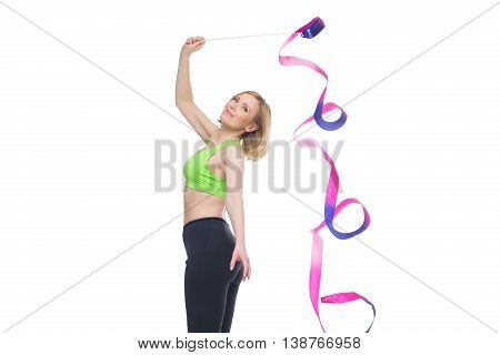 Beautiful middle aged blond fit woman in green bra top and black pants doing sport exercise with gymnastic ribbon. Isolated over white background. Copy space.