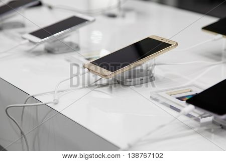 New smartphones on a white showcase with antitheft system