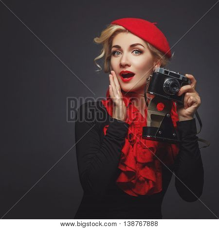 Beautiful young woman in red beret holding retro photo camera. Surprised expression. Red lips. Over black background. Copy space.